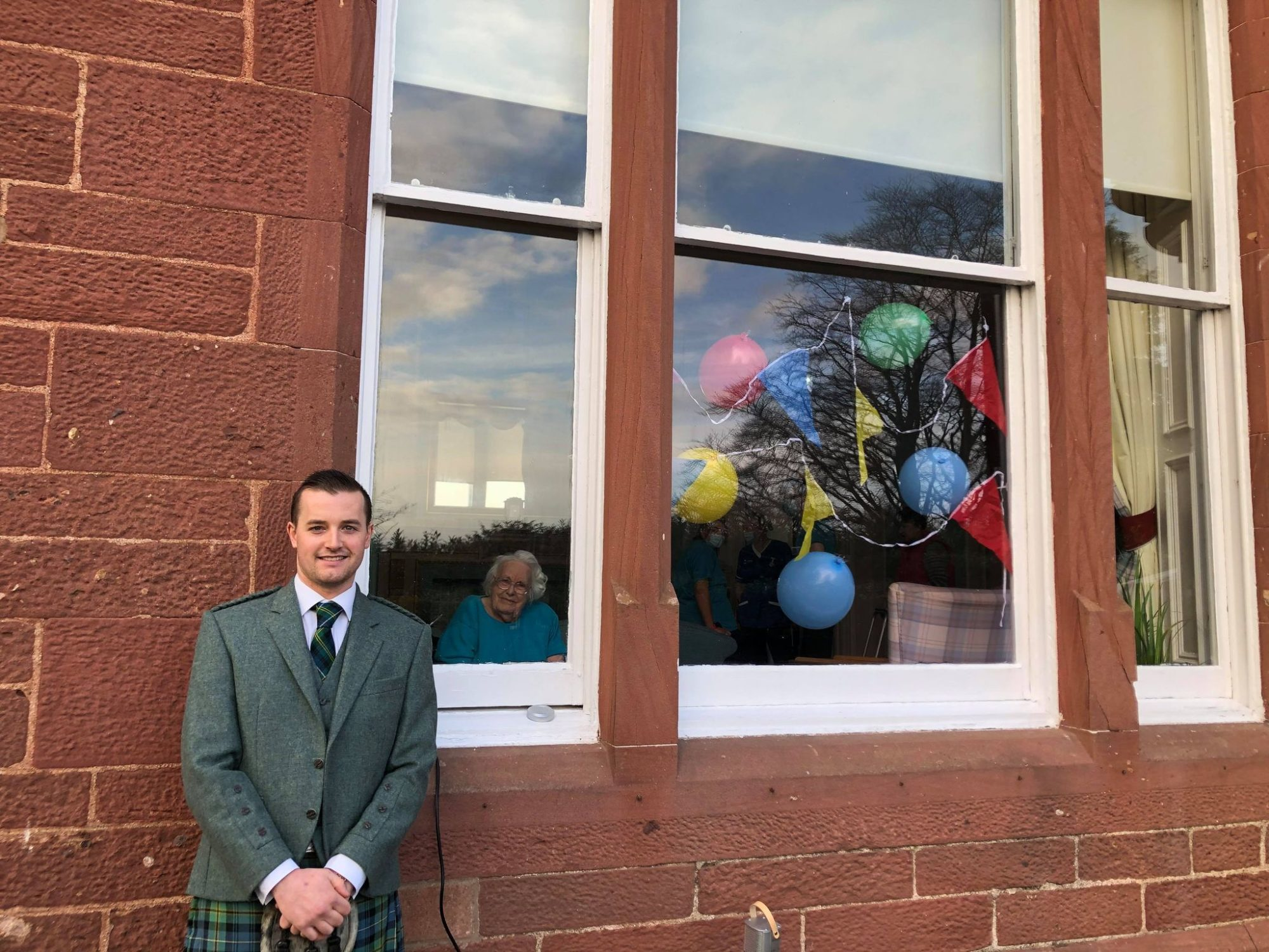 Grandson and his bride delight grandmother with care home window visit on wedding day